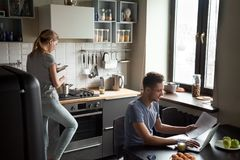 Young couple using laptop and smartphone in the kitchen royalty free stock image