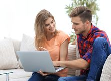 Young couple is using a laptop and smiling while sitting on sofa at home Stock Image