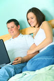 Young Couple Using Laptop On Their Bed Royalty Free Stock Photography
