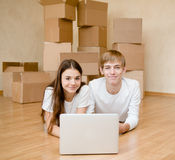 Young couple using laptop in their new home Stock Photos