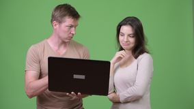 Young couple using laptop and thinking together. Studio shot of young handsome Scandinavian man and young beautiful woman together against chroma key with green stock footage