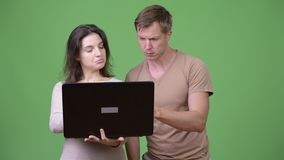 Young couple using laptop and thinking together. Studio shot of young handsome Scandinavian man and young beautiful woman together against chroma key with green stock video footage