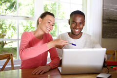 Young couple using laptop together at home. Portrait of happy young couple sitting at a table and using laptop together Stock Image