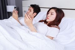 Young couple using mobile phone on bed in bedroom. Young couple using mobile phone on bed in the bedroom Royalty Free Stock Photography