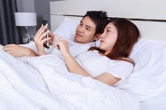 Young couple using mobile phone on bed in bedroom. Young couple using mobile phone on bed in the bedroom Stock Image