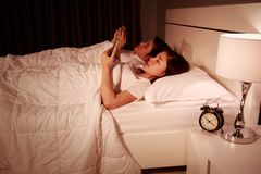 Couple using mobile phone on bed at night. Young couple using mobile phone on bed at night Stock Photos