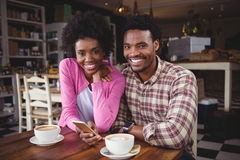 Young couple using mobile phone in cafeteria Royalty Free Stock Photo