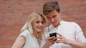 A Young Couple Using a Mobile Phone Outdoors Royalty Free Stock Images