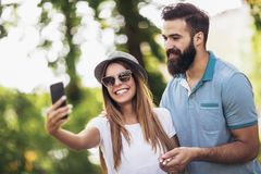 Couple using mobile phone taking a selfie in the park royalty free stock photography