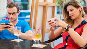 Young couple using mobile phones in a cafe. Stock Images