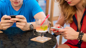 Young couple using mobile phones in a cafe. Royalty Free Stock Photo