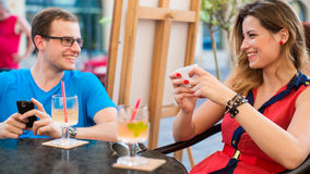 Young couple using mobile phones in a cafe. Royalty Free Stock Image