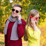Young couple using a mobile phones. Young couple talking themselves by mobile phone. Stock Photography