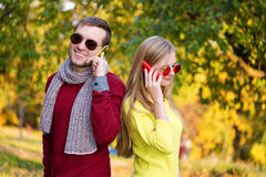 Young couple using a mobile phones. Young couple talking themselves by mobile phone. Royalty Free Stock Photo
