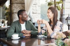 Young couple using mobile smartphones in cafe. Young multiracial couple using mobile smartphones in cafe. Travel people sharing media in social networks with Stock Photos