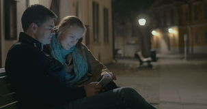 Young couple using pad on the street bench. Young couple sitting on the bench in quiet street. They using tablet computer in dim light of lanterns in chilly stock video footage