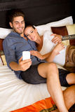 Young couple using phone in a asian hotel room Stock Photo