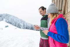 Young Couple Using Smart Phone Snowy Village Wooden Country House Man And Woman Online Messaging Winter Snow. Resort Cottage Holiday Vacation Stock Images