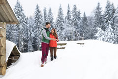 Young Couple Using Smart Phone Snowy Village Wooden Country House Man And Woman Online Messaging Winter Snow. Resort Cottage Holiday Vacation Royalty Free Stock Image