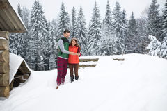 Young Couple Using Smart Phone Snowy Village Wooden Country House Man And Woman Online Messaging Winter Snow. Resort Cottage Holiday Vacation Royalty Free Stock Photography