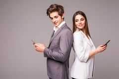 Young couple is using smart phones and smiling while standing back to back on a gray background. Look at camera. Young couple is using smart phones and smiling royalty free stock photos