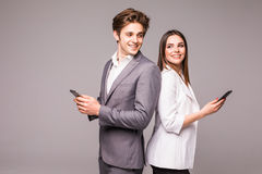 Young couple is using smart phones and smiling while standing back to back on a gray background. Look each other. Young couple is using smart phones and smiling royalty free stock image