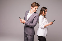 Young couple is using smart phones and smiling while standing back to back on a gray background. Man look at woman. Young couple is using smart phones and royalty free stock photos
