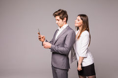 Young couple is using smart phones and smiling while standing back to back on a gray background. Woman look at man. stock images
