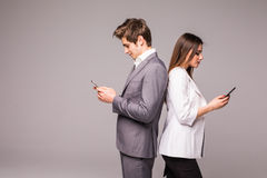 Young couple is using smart phones and smiling while standing back to back on a gray background. Young couple is using smart phones and smiling while standing stock image