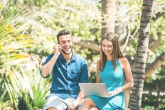 Young couple using smartphone and computer while sitting in a park outdoor - Handsome man having a phone call and beautiful girl stock images