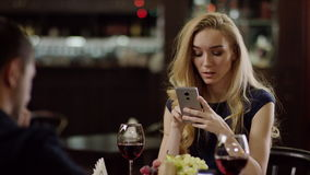 Young couple using smartphone during dating in restaurant. Pair using smartphone during dating in restaurant. lovers with mobiles stock video footage