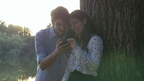 Young couple using the smartphone in the park stock video footage
