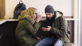 Young couple using smartphone sitting in cafe in city.  stock footage