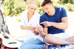 Young couple using smartphones at the beach Stock Images
