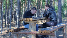 Young couple using smartphones and chatting. Having rest in autumn park forest. Young couple using mobile phones and chatting. Having rest in autumn park forest stock video footage