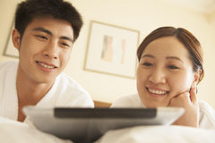 Young Couple Using Tablet in Bed Stock Image