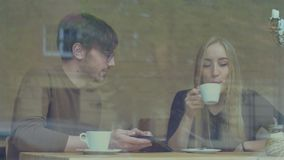 Young Couple Using a Tablet in the Cafe. A girl and a guy sitting at a table in the cafe and use a tablet together and talking stock video footage