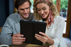Young couple using tablet computer at table in cafeteria Stock Photography