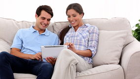 Young couple using tablet. On a couch stock video