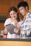 Young Couple Using Tablet in Kitchen Royalty Free Stock Images