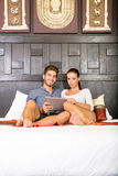 Young couple using a Tablet PC in a asian hotel room Royalty Free Stock Photos