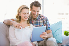 Young couple using tablet pc on the couch Royalty Free Stock Images