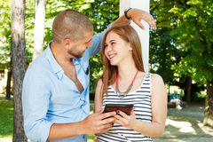 Young couple using a tablet PC in the park Royalty Free Stock Photo