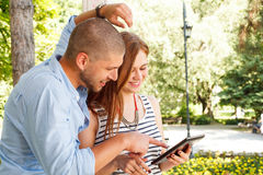 Young couple using a tablet PC in the park Stock Photo