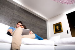 Young couple using a Tablet PC together on the Sofa at home Royalty Free Stock Photography
