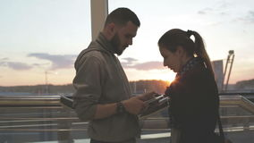 A young couple using a tablet at sunset. A couple using a tablet at sunset. A young couple using a tablet at sunset. They stand near a window and talk stock video