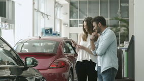 Young couple using a telephone in car showroom. Swarthy guy and beautiful girl stands in the car showroom. Young couple is looking on the screen of smartphone stock video