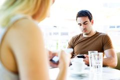Young couple using their mobile phones while sitting at cafe. Beautiful couple using their mobile phones while sitting at cafe - date Stock Image