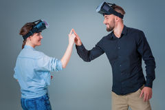 Young couple using VR headsets on grey background Stock Photos