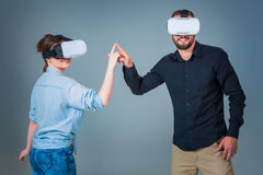 Young couple using VR headsets on grey background Stock Image